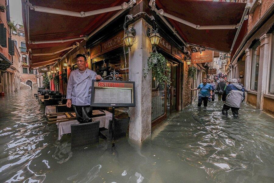 Bir restoran sahibi kara kara  sel sularının ne zaman çekileceğini düşünüyor.