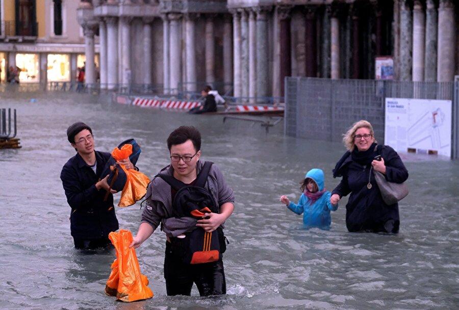Turistler ayakkabılarını poşete koyarak sel suları içinde ilerliyorlar.