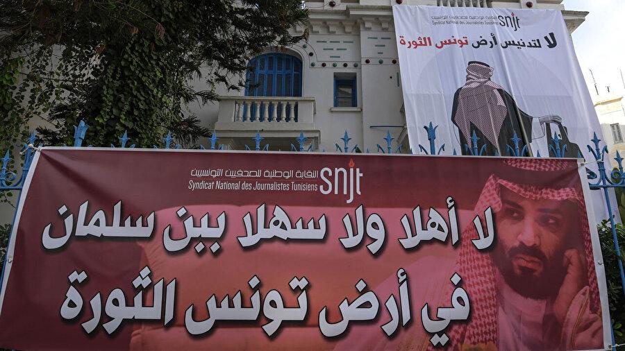 """""""Devrim toprağı Tunus'un kirletilmesine, hayır"""" Suudi gazeteci Cemal Kaşıkçı'nın öldürülmesinden sonra ilk yurt dışı turuna çıkan Suudi Arabistan Veliaht Prensi Muhammed bin Selman'ın ülkelerine gerçekleştireceği ziyarete karşı, Tunuslular protesto gösterisi gerçekleştirdi. Başkentin merkezinde bulunan Habib Burgiba Caddesi'ndeki Belediye Tiyatrosu önünde toplanan yüzlerce gösterici, Suudi gazeteci Cemal Kaşıkçı'nın öldürülmesinden sonra ilk yurt dışı turuna çıkan Bin Selman'ın Tunus ziyaretine karşın """"Tunus toprağını kirletmeye hayır"""" çağrısıyla protesto gösterisi düzenledi."""