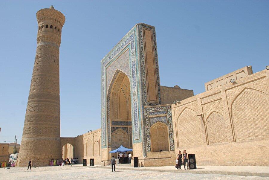 """Kelan Minaresi Buhara'nın en önemli sembollerinden Kelan (Büyük) Minaresi, şehirdeki en yüksek yapı olarak yerli ve yabancı turistlerin dikkatini çekiyor. Yaklaşık 47 metre yüksekliğinde ve bölüm bölüm her kuşağında farklı desenlerin işlendiği bu minare, halk dilinde """"Minare-i Kelan"""" olarak adlandırılıyor. Orta Asya'nın en görkemli ve yüksek minaresi olan yapının bazı kesimleri turkuaz çinilerle işlenmiş ve minarenin gövdesinin orta kısmı kufi yazıyla süslenmiş.          Geçmişte şehre gelen kervanların yollarını kolay bulması için minarenin tepesinde geceleri ateş yakıldığı rivayet ediliyor."""
