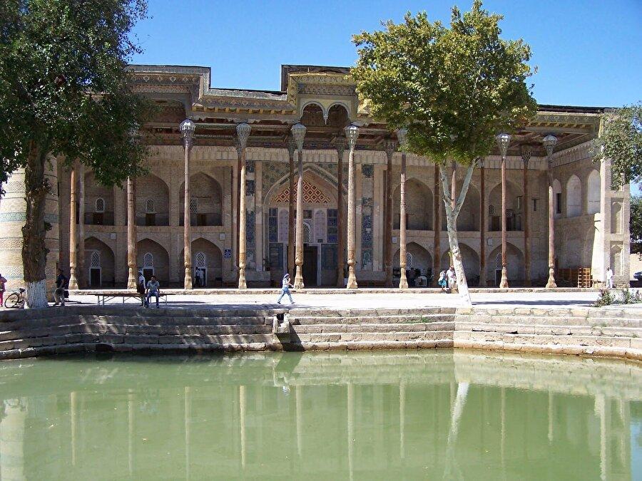 Leb-i Havuz Şehrin merkezinde yer alan Leb-i Havuz kompleksi, Buhara'da görülmesi gereken en önemli yerlerin başında geliyor. Bu kompleksin içinde medrese cami de bulunurken, ortadaki havuzun kenarında ise Nasrettin Hoca'nın heykeli yer alıyor. Leb-i Havuz olarak bilinen yer tarih boyunca kervanların en önemli uğrak yerlerinden olmuş. Kompleks bünyesinde yer alan medreselerden Nadir Divan Bey Medresesi'nin giriş kapısında hayvan ve güneş figürlerinin yanı sıra Kur'an-ı Kerim'den ayetlere yer verildiği görülüyor.          Rivayetlere göre, Vezir Nadir Divan Bey 1619-1620'de buraya bir kervansaray yaptırıyor. Daha sonra Nadir Divan Bey, kervansarayın yapımı tamamlanınca bu güzel eseri göstermek için Han'ı davet ediyor. Han'ın eseri görünce medreseye benzetmesi üzerine vezir, ustalara süslemelerin medrese süslemelerine benzetilmesi talimatı veriyor.          Medresenin içindeki dükkanlarda ise günümüzde Özbekler, ata mirası demircilik zanaatını icra ediyor ve en güzel örneklerini sergiliyor.          Öte yandan, kompleksin etrafında turistlerin ilgisini çekebilecek oldukça güzel restoranlar ve rengarenk yöresel hediyelik eşyaların satıldığı dükkanlar bulunuyor. Bir yandan Özbek mutfağının lezzetlerinin tadına bakarken, bir yandan da Özbek şarkılarını dinleyebileceğiniz bu restoranlarda fiyatlar da oldukça makul.          Leb-i Havuz'un çevresinde gezinirken, binaların iç ve dış cephesinde modernizmin etkisinden uzak, Orta Asya kültürüne ait kullanılan motifler de şehrin tarihi dokusunu korumasına katkı sağlamış.