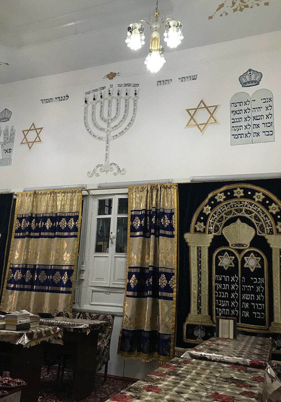"""Orta Asya'da """"Buhara Sinagogu"""" Tarih boyunca farklı kültür ve inançlara ev sahipliği yapmış Buhara'nın dar sokaklarında gezinirken yaklaşık 400 yıl önce inşa edilmiş bir sinagoga rastlamak mümkün.Günümüzde az sayıda Yahudi ailenin yaşadığı mahallede yer alan sinagogun ortasında bir avlu, avlunun iki yanında oturma yerleri, duvarda resmedilmiş 7 kollu şamdan, hahamların fotoğrafları ve çok eski Tevratlar bulunuyor.          Farklı kaynaklarda, burada yaşayan Yahudilerin binlerce yıl önce Orta Asya'ya geldiğine dair ifadeler bulunuyor. Zaman içinde dünyanın birçok yerine dağılan bu Yahudi cemaatinden şu anda Özbekistan'da küçük bir topluluk kalmış olsa da geri kalanlar bu toprakları terk etmeyerek vatan edinmiş.Şehirde, sinagogun yanı sıra bir de Yahudi okulu bulunuyor."""