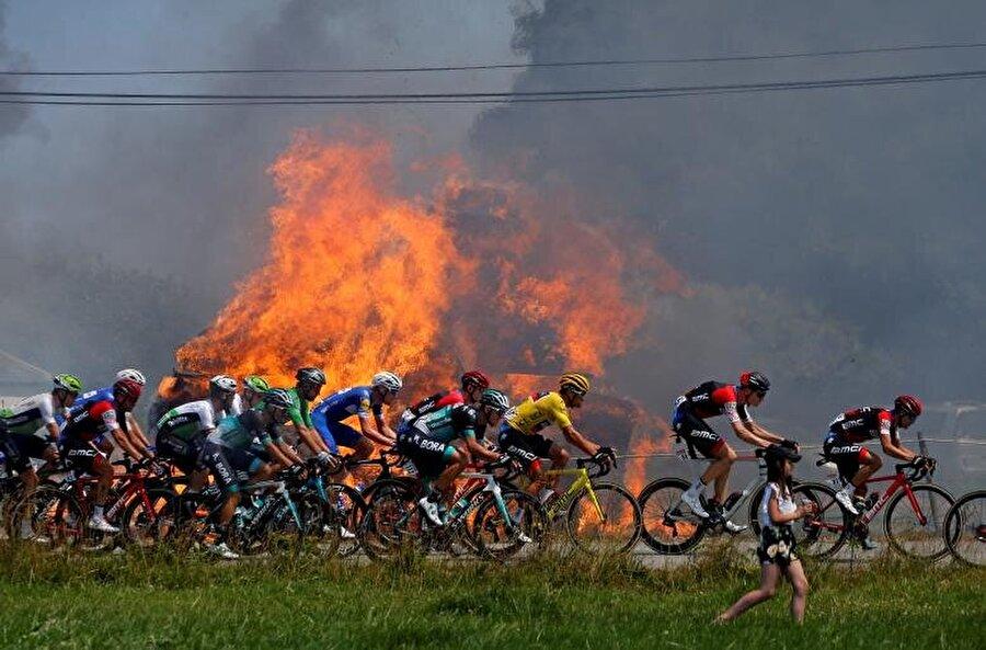 Fransa Bisiklet Turu'nun altıncı etabında minik bir yangının yanından geçen öncü grup.                                                                           REUTERS/Stephane Mahe