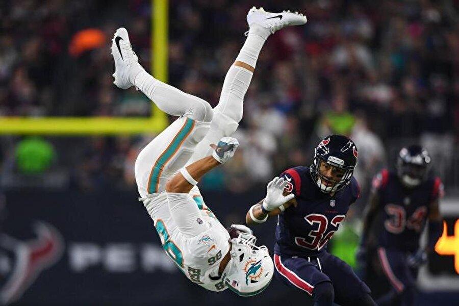 Miami Dolphins forması giyen Mike Gesicki, Kareem Jackson tackle'ı sonrasında takla atıyor.                                                                           USA TODAY Sports/Shanna Lockwood