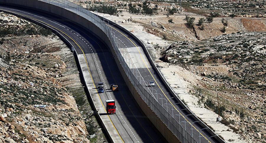 """İsrail Batı Şeria'da """"Utanç Yolu""""nu açıyor İsrail tarafından açılan yeni otoyol, İsrail vatandaşları tarafından memnuniyetle karşılanırken, Filistinlilerin tepkisini üzerine çekti. """"Utanç Yolu"""" olarak tanımlanan bu yol, İsrail vatandaşları ve Filistinlilerin kullanacağı yolları ayırmak için tasarlandı. Yolun kullanıma hazır ilk bölümü Kudüs bölgesine ulaşımı sağlıyor ancak bunu yaparken İsrailli ve Filistinliler için iki farklı güzergah oluşturuyor. Yol, İsrailli vatandaşlar için kontrol noktalarından kaçınarak doğrudan Kudüs'e varmayı olanaklı kılarken, Filistin vatandaşlarını ise kontrol noktalarına yönlendiriyor."""