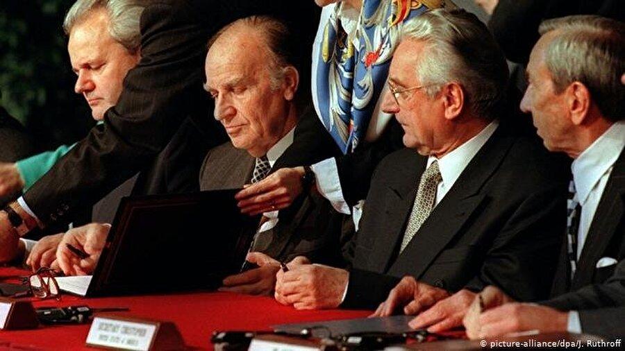 Bosna Savaşı'nı bitiren anlaşma, 1995'te ABD'nin Ohio eyaletindeki Dayton Hava Üssü'nde imzalandı                                                                                                                                                                                          İkinci Dünya Savaşı'ndan sonra Avrupa'nın gördüğü en ağır soykırımın yaşandığı Bosna Savaşı'nı bitiren anlaşma, Tarihler 1995'i gösterdiğinde ABD'nin Ohio eyaletindeki Dayton Hava Üssü'nde imzalandı.  Anlaşma, Amerikalı diplomat Richard Halbrooke'un girişimleriyle Bosna-Hersek Devlet Başkanı Aliya İzzetbegoviç, Sırbistan Devlet Başkanı Slobodan Miloşeviç ve Hırvatistan Devlet Başkanı Franjo Tudjman tarafından imzalandı. Bu anlaşma silahları susturdu; ancak ülkeyi siyasi bir düğümle baş başa bıraktı. Zira 15 yıl öncesine kadar birbirleriyle savaşan üç etnik yapı, bu anlaşmayla tek bir çatı altında, ülkenin kurucusu olarak görev aldı.