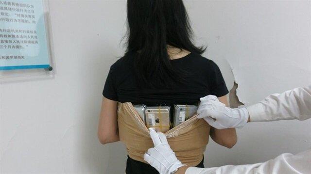 Çinli kadın üzerine sardığı 102 iPhone'la yakalandı