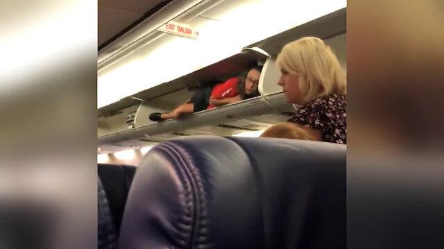 Kabin görevlisi uçaktaki bagaj bölümüne yatarak yolcularla sohbet etti