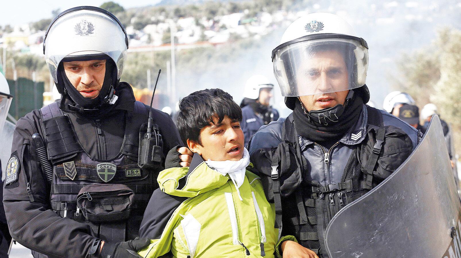 Yunanlar yerde darp ettikleri göçmen çocuğu daha sonra gözaltına aldı.
