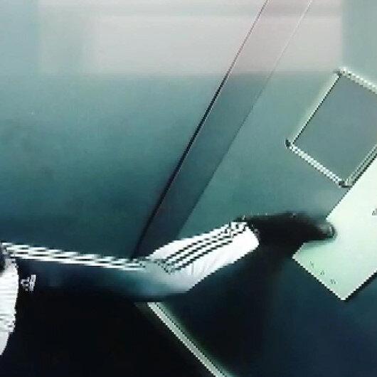 Asansör düğmesine ayağıyla basan kişi güvenlik kamerasında