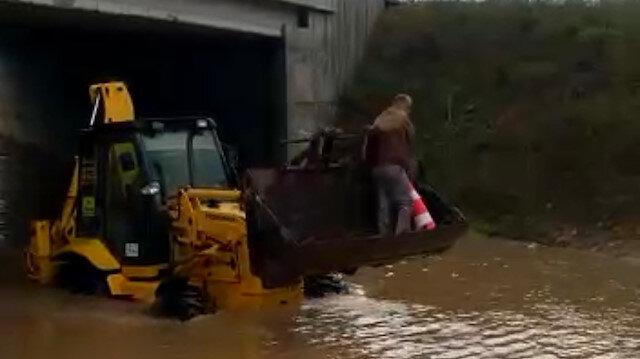 Su basan alt geçitte aracıyla mahsur kalan taksici, kepçeyle kurtarıldı