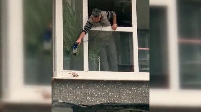 Sultangazi'de yürek ısıtan görüntü: Soğuktan titreyen kumruyu camdan uzattığı saç kurutma makinesiyle ısıttı