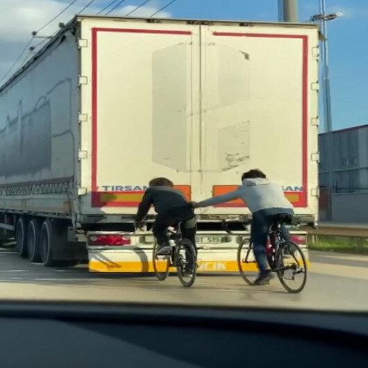 Bursada TIRın arkasına tutunan bisikletli gençlerin tehlikeli yolculuğu kamerada