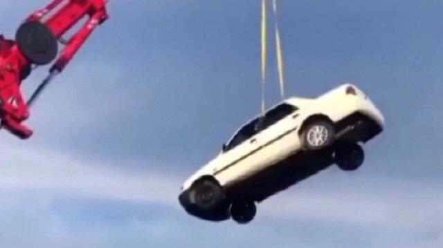 Metrelerce yükseklikteki vince bağlanan otomobilde canlarını tehlikeye attılar