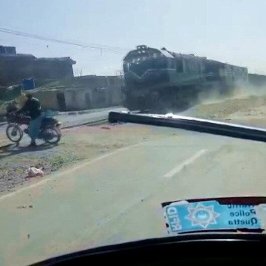 Pakistanda motosiklet sürücüsü, trenin altında kalmaktan saniyelerle kurtuldu