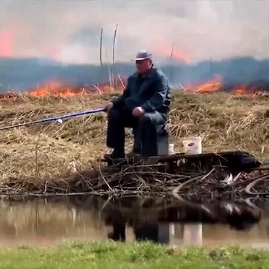 Yanı başındaki yangına aldırış etmeyerek balık tutmaya devam etti