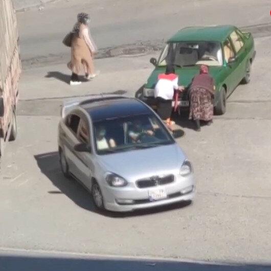 Yolda kalan aracı gören kağıt toplayıcısı kadın otomobili iterek yardımcı oldu