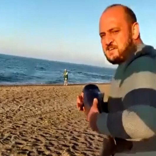 Gölde bulduğu yavru yunus balığını kucağına alarak denize taşıdı