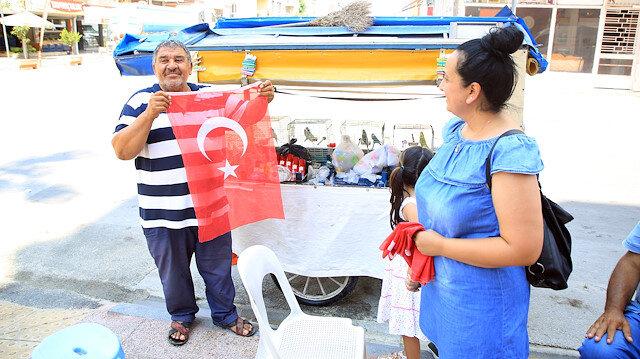 Çöpte bulduğu bayrakları temizleyip 15 Temmuz için esnafa dağıttı