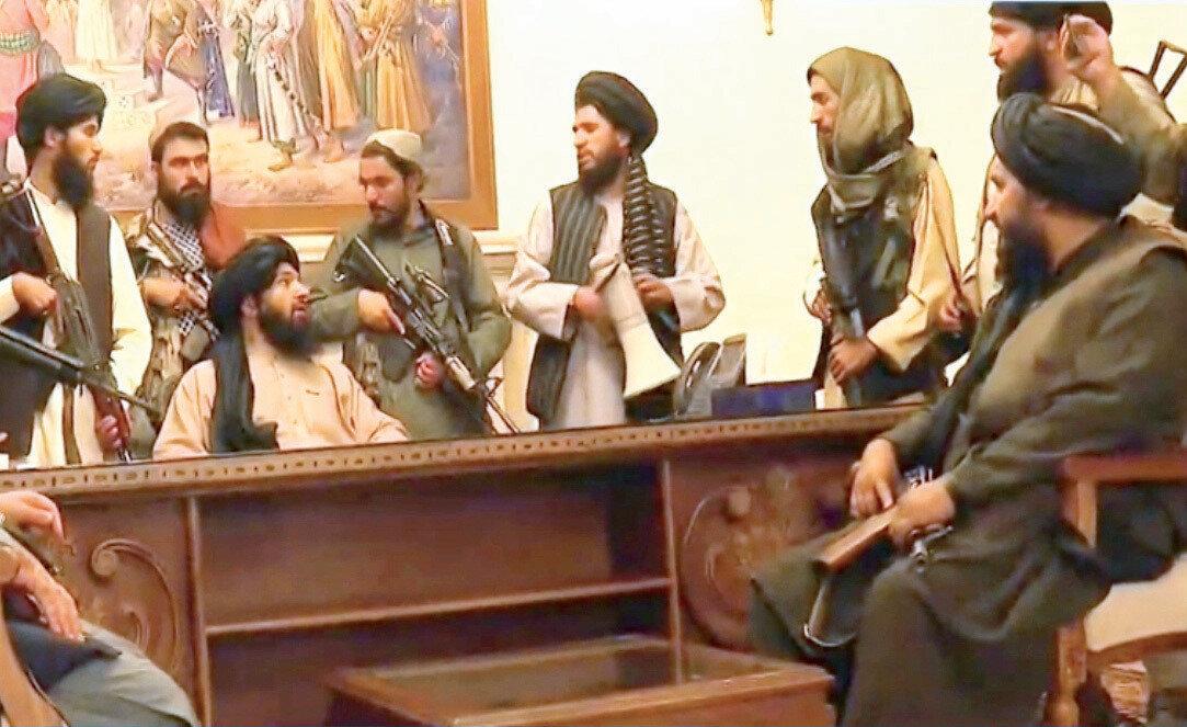 Taliban güçleri Başkanlık sarayını ele geçirdikten sonra Devlet Başkanı Gani'nin makamında poz verdi.