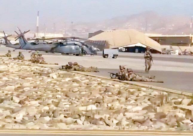 ABD askerlerinin havalimanında sivil Afganlara karşı elleri tetikte beklediği görüldü.