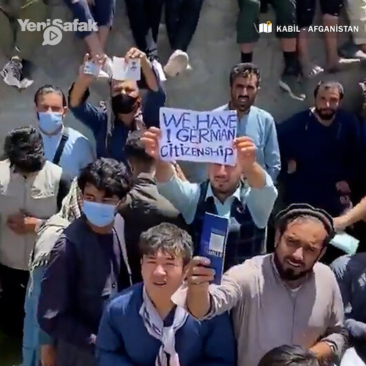 Alman vatandaşıyız yazılı pankart taşıyan Afganlar kanalizasyon hattı içinde tahliye sırasına girdi