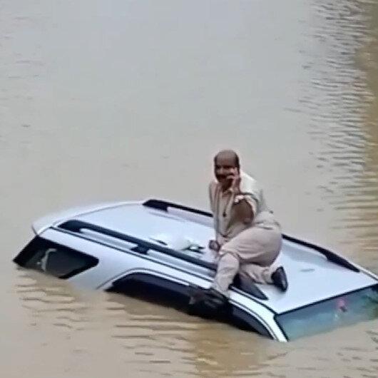 Hindistan'da sele kapılan sürücü aracının üzerinde kurtarılmayı bekledi