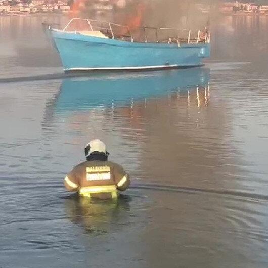 Balıkesirde itfaiyeciler tekneyi söndürmek için kıyafetleri ile denize girdi