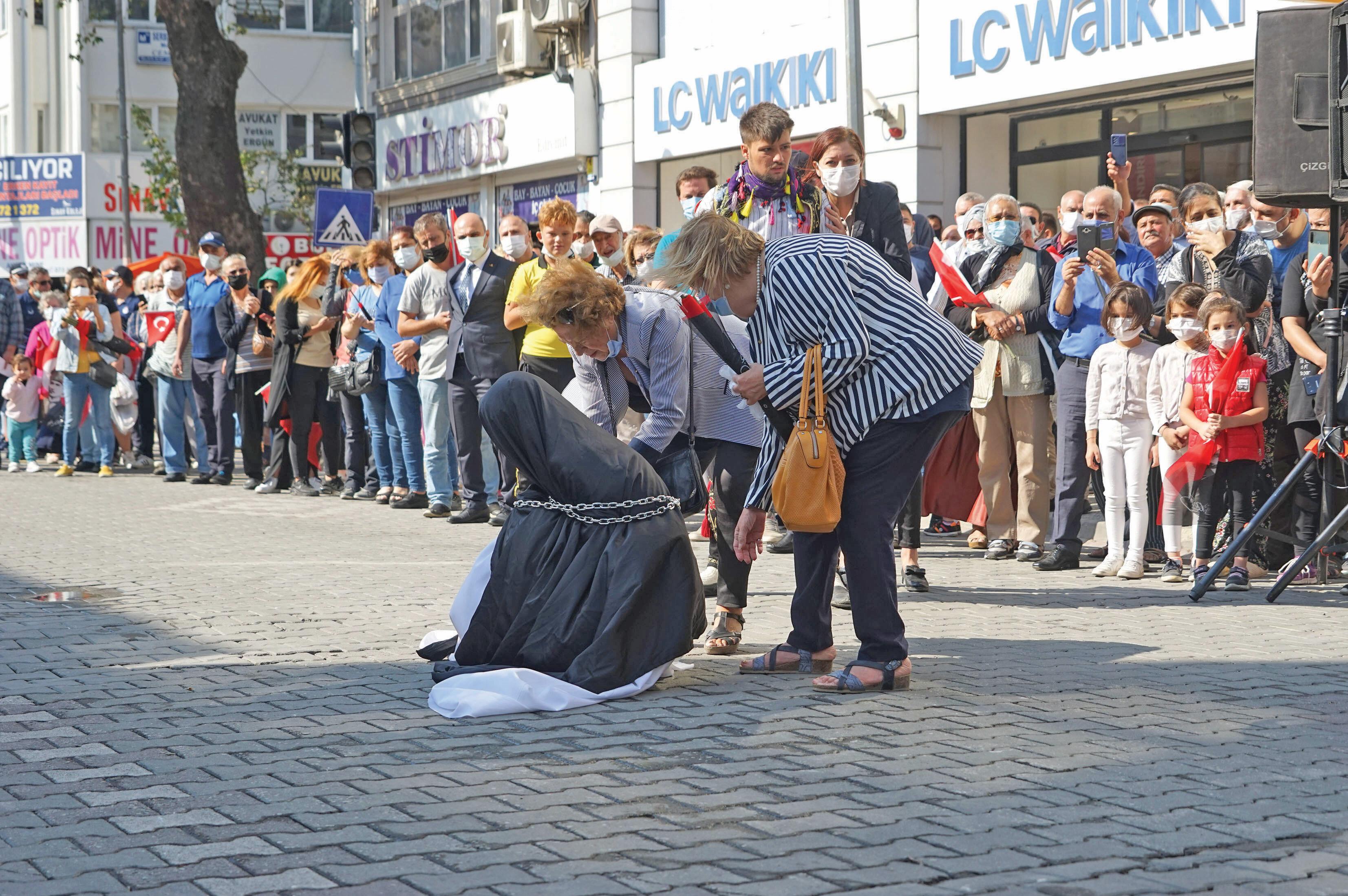 Törende zincire vurulan çarşaflı bir kadına diz çöktürüldü.