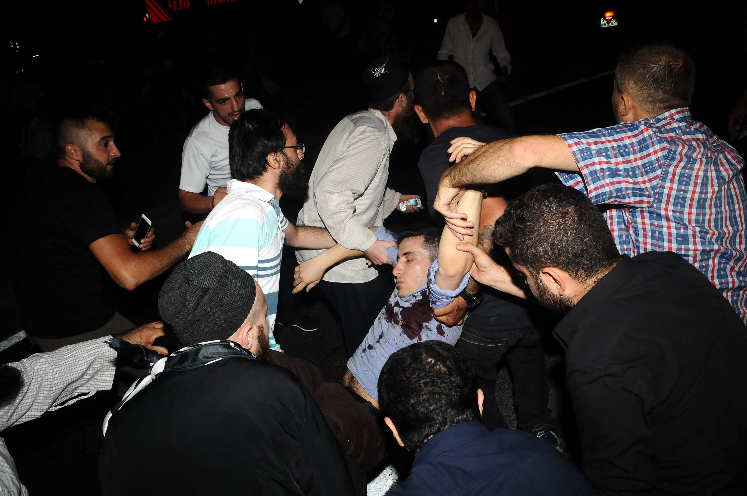 A civilian injured in gunfire is carried to an ambulance.