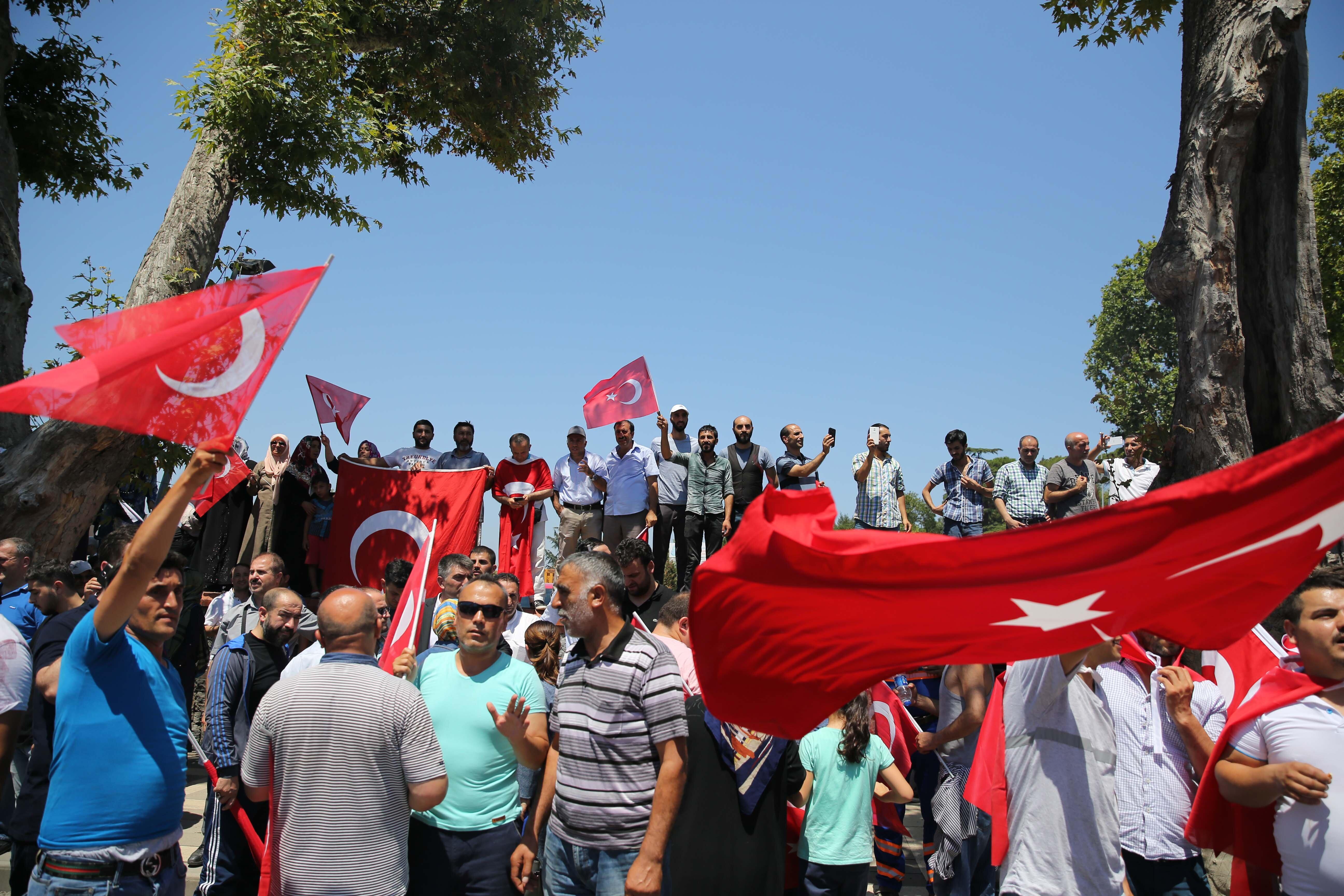 Vatandaşlar ellerinde Türk bayraklarıyla bekliyor.