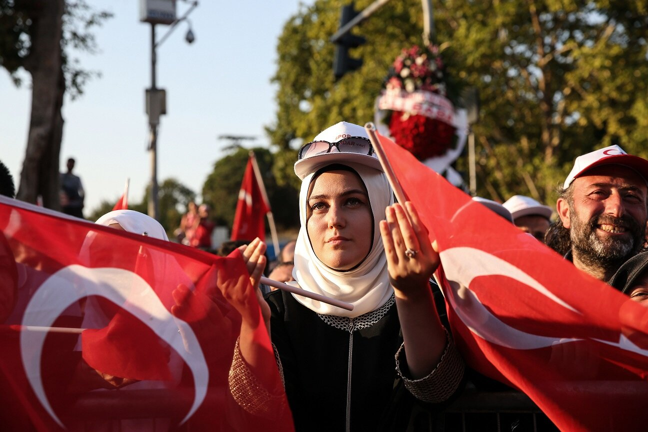 A citizen praying with a Turkish flag.